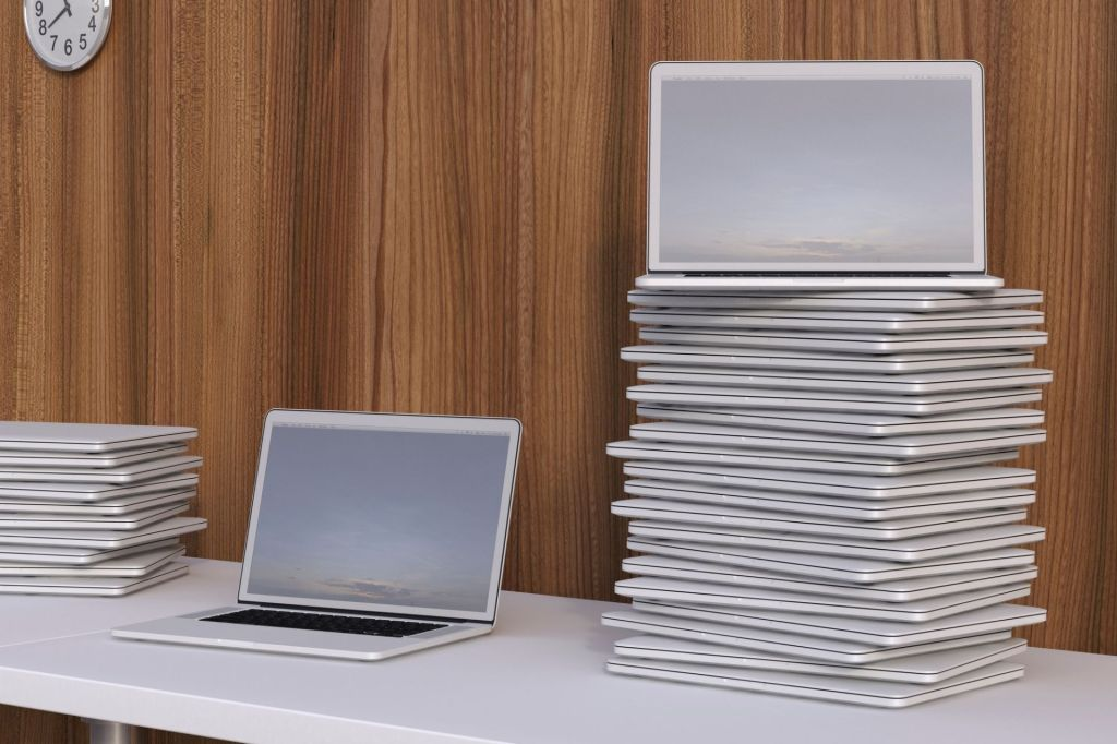 Stack of refurbished laptops on white table