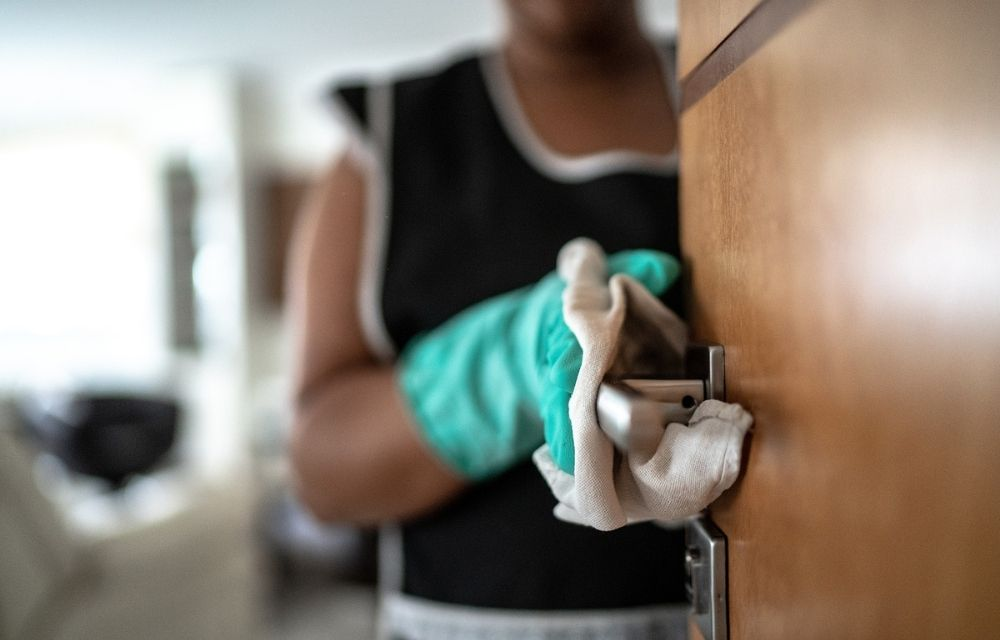 Hospitality worker cleaning doorknob