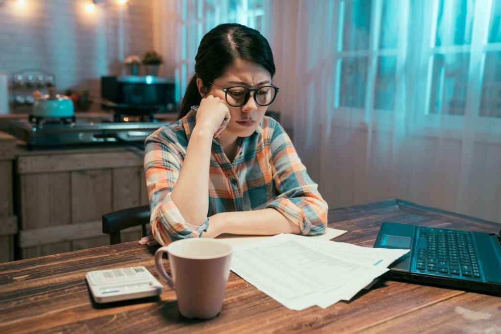 Worried woman sits at wooden kitchen table